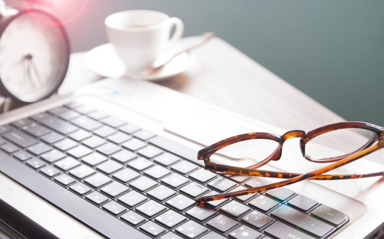 A pair of glasses rest on a laptop keyboard, the laptop itself is on a desk. A clock and a cup of coffee in the background