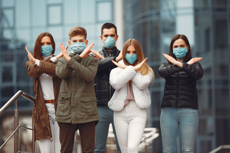 Crowd of people wearing surgical masks, crossing their arms in an X shape