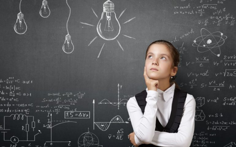 Girl thinking in front of a blackboard with formuals written.