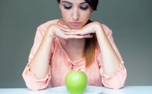 Woman staring down on green apple