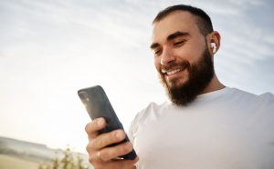 Smiling jogger checking SMS marketing messages about BFCM on his smartphone